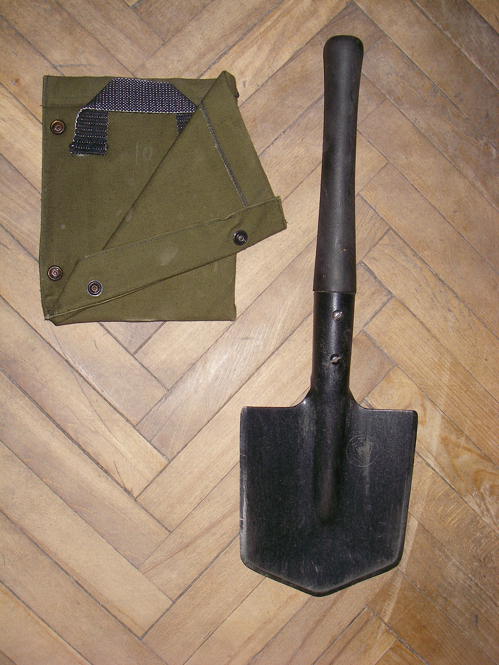 Post-WWII design. The blade cover to the left allows wearing the MPL-50 on the belt, in the blade up orientation.
